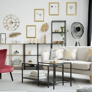 Wine red armchair, metal tables and beige sofa standing on a striped rug in white living room interior