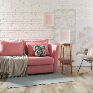 Stylish living room interior with sofa and rocking armchair near brick wall