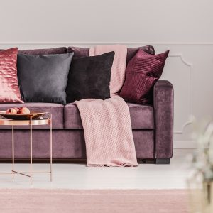Copper table in front of a violet couch with decorative pillows in elegant living room interior